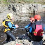 Instructor teaching two men about hydrospeeding on the River Tees